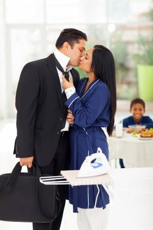 loving husband kissing wife before going to work photo