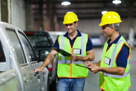 dispatch: shipping company workers inspecting vehicle before dispatch Stock Photo