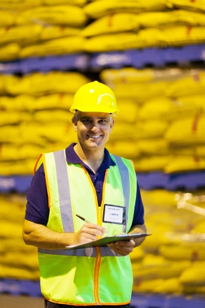 shipping company senior worker recording pallets in warehouse photo