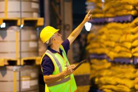 food distribution: middle aged shipping company worker counting pallets in warehouse before dispatching