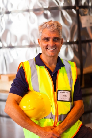 portrait of senior shipping company worker holding his helmet in warehouse Stock Photo - 20665708