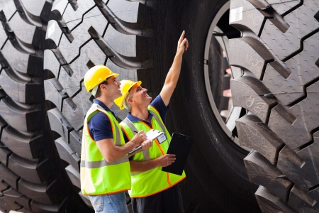 inspecting: shipping company workers checking industrial tires before exporting Stock Photo