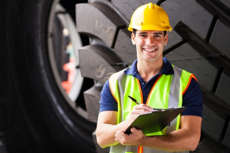 portrait of shipping company employee standing in front of industrial tires Stock Photo