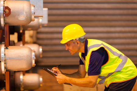 smiling senior shipping worker inspecting machinery at warehouse Stock Photo - 20667394