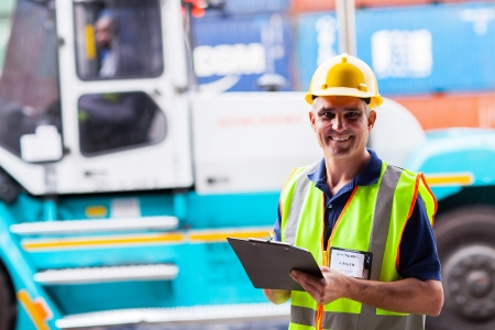 happy middle aged shipping worker standing big forklift Stock Photo - 20667418