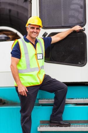 forklift driver: senior harbor forklift driver standing on forklift in container depot