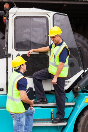 middle aged forklift driver talking to co-worker photo