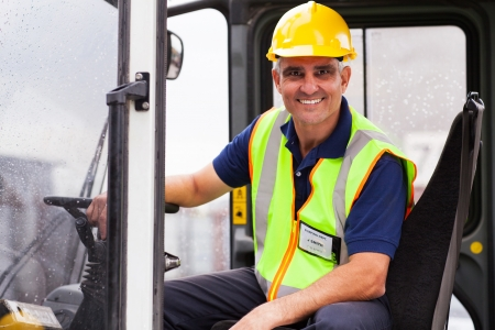 skilled operator: cheerful middle aged forklift operator
