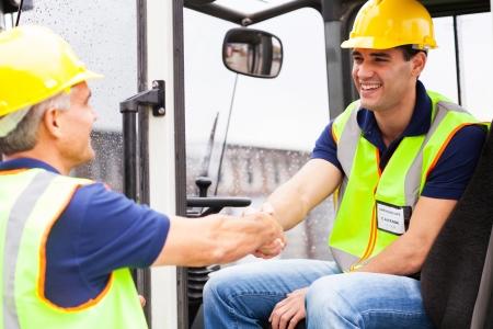 carretillas almacen: dos conductores de carretillas elevadoras de almac�n apret�n de manos cuando el cambio de turno sobre