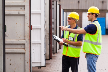 smiling warehouse workers checking open containers before loading Stock Photo - 20667583