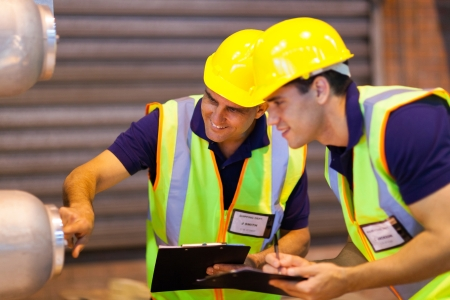 safety gear: warehouse co-workers in safety gear inspecting machinery Stock Photo