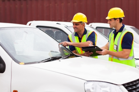 inspecting: shipping company workers inspecting cars outdoors before exporting