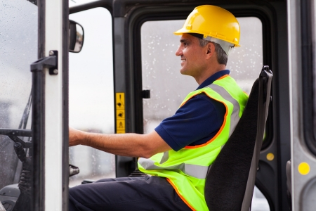 middle aged professional warehouse worker operating forklift Stock Photo - 20660156