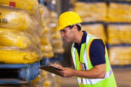 industria alimentaria: sonriente joven trabajador de grabaci�n de existencias de arroz antes de la entrega Foto de archivo