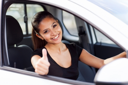 girl looking up: beautiful businesswoman giving thumb up inside her new car