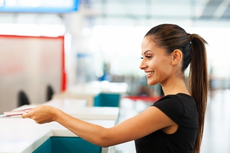 over the counter: attractive businesswoman handing over air ticket at airport check in counter Stock Photo