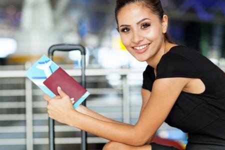vrolijke zakenvrouw wachten op haar vlucht op de luchthaven