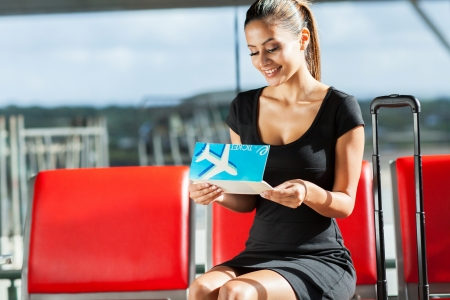 happy young businesswoman looking at her air ticket