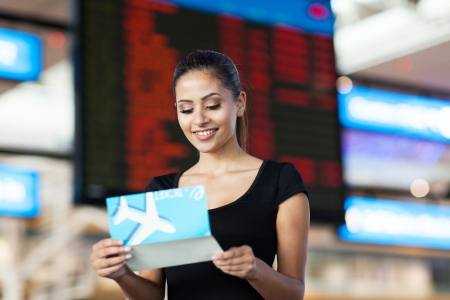 well read: smiling young business woman looking at air ticket in airport