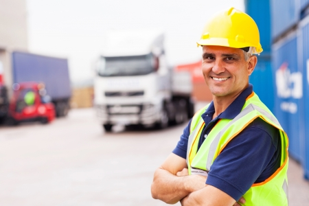cheerful senior shipping company worker standing outside warehouse with arms crossed photo
