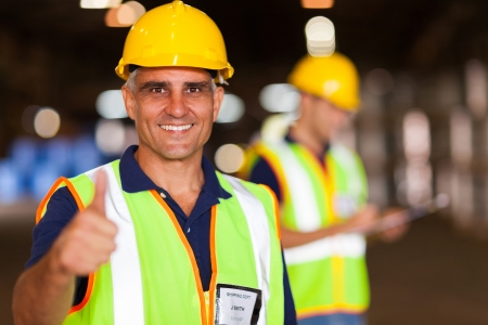 senior shipping company worker giving thumb up inside warehouse photo