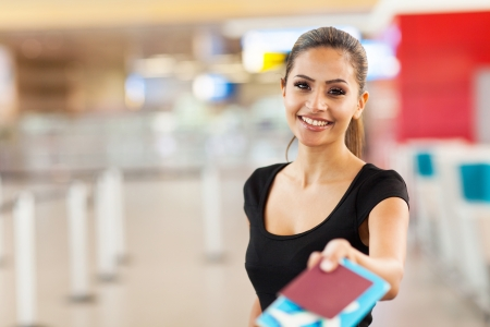 travellers: beautiful businesswoman handing over passport and air ticket at airport check in counter