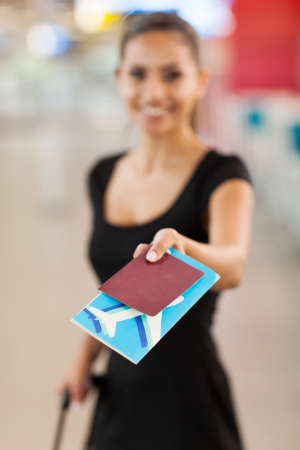 check in: smiling young businesswoman presenting air ticket and passport at airport