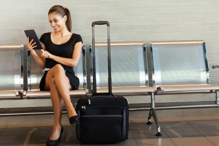 美しい若い女性は空港でタブレット コンピューターを使用して
