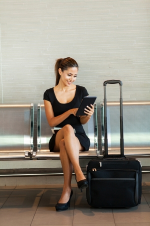cheerful business woman using tablet computer at airport photo