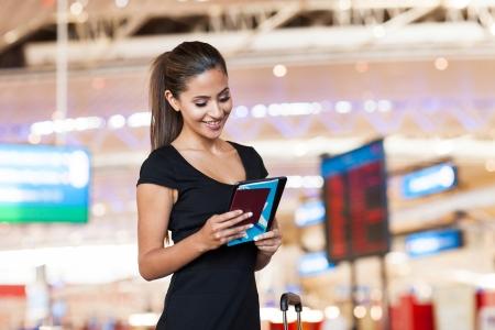 pasaporte: sonriente joven mujer de negocios en el aeropuerto de leer sus mensajes de correo electrónico en el ordenador tableta
