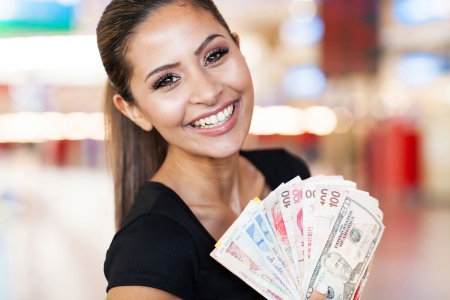 rand: happy young woman holding fan of cash on casino background
