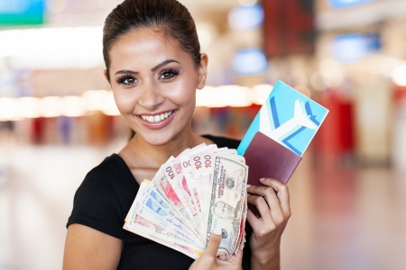 beautiful young woman holding passport, air ticket and cash at airport  photo