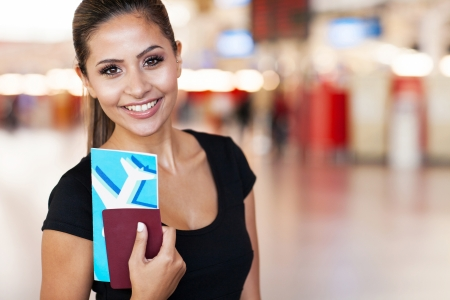 close up portrait of young businesswoman at airport holding flight ticket photo