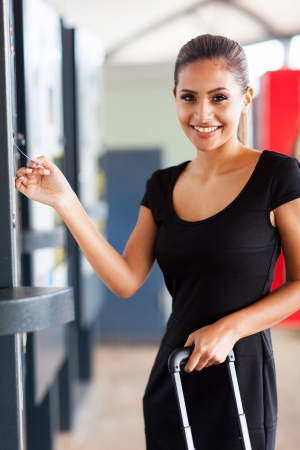 attractive young woman paying parking ticket at airport photo