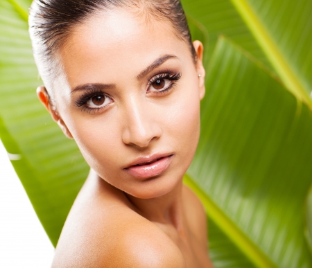 girl face close up: young cute woman with clean skin over green leaf