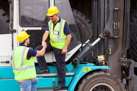 smiling forklift driver handshaking with colleague photo
