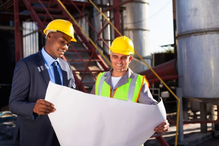 petrochemicals: industrial engineers standing in front of a large oil refinery machinery with blueprint on hand