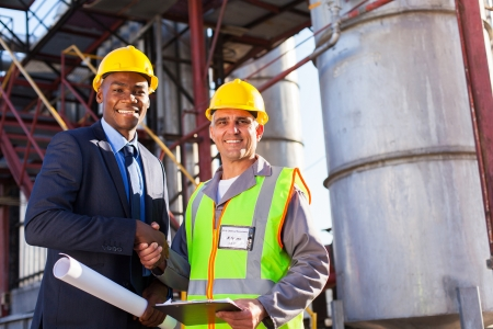 cheerful african refinery manager handshaking with senior worker in front of fuel-tanks Stock Photo - 20668220