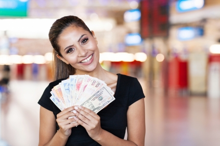 rand: attractive young woman holding cash outside casino Stock Photo