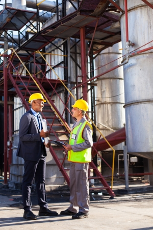 african petrochemical manager in discussion with plant worker outdoor photo