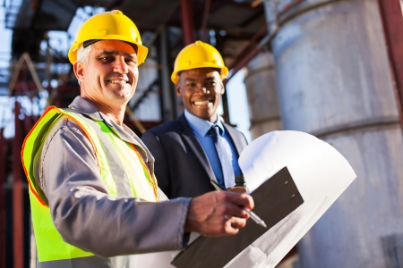 petroleum: senior oil industry worker holding clipboard and blueprint with manager in plant Stock Photo