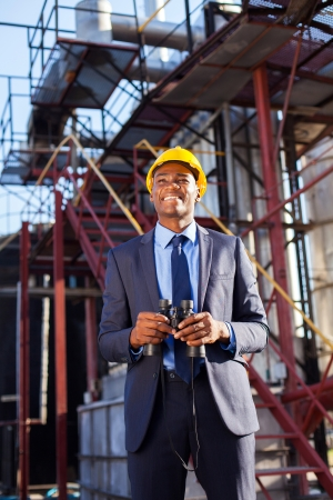 cheerful african industrial manager with binoculars in fuel refinery photo