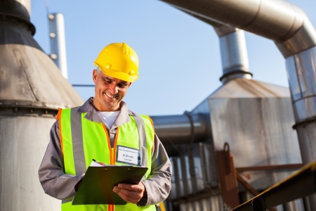 petrochemical plant: smiling senior petrochemical engineer recording technical data on clipboard Stock Photo