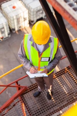 industria quimica: un agente superior de qu�mica del aceite de trabajo en la planta de refiner�a Foto de archivo