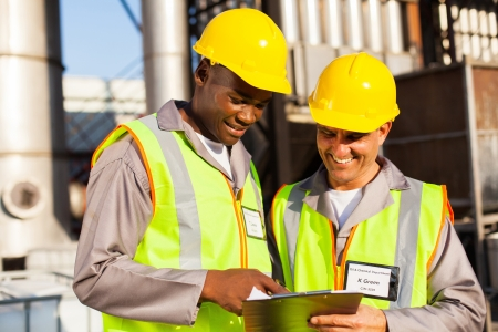 two heavy industry workers working in plant Stock Photo