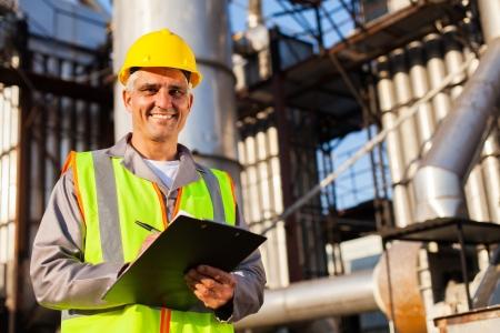 petrochemie industrie: gelukkige midden oude olie-industrie werknemer in raffinaderij Stockfoto