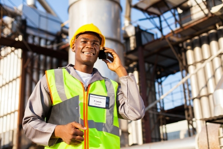 blue collar: african oil and chemical worker talking on cell phone