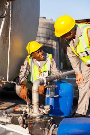 industria quimica: dos trabajadores petroquímicos inspeccionar válvulas de presión en un tanque de combustible