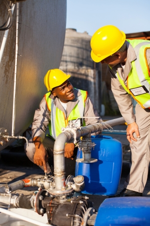 two petrochemical workers inspecting pressure valves on a fuel tank  Stock Photo