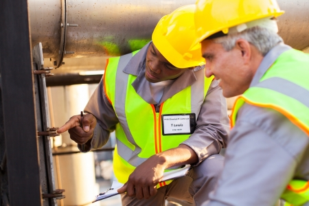 two mechanical engineers working on fuel pipeline in plant photo